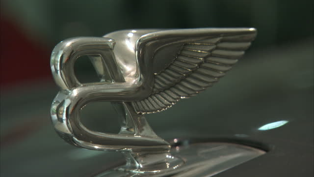A winged Bentley hood ornament decorates a luxury car.