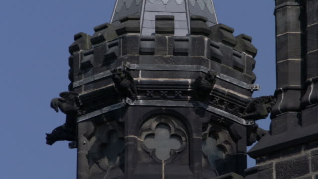 Winged creatures decorate the points on an octagonal tower of a house. Available in HD.