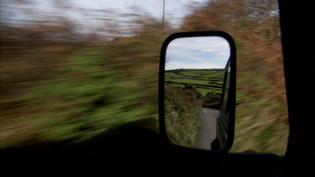 A wing-mirror reflects the country road. Available in HD.