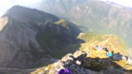 POV of wingsuit flier jumping from mountain summit