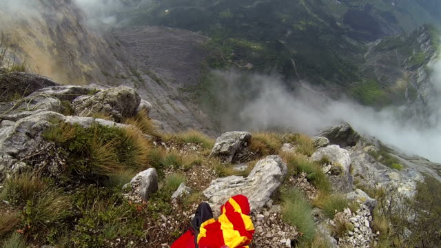 Wingsuit flier prepares to descend from cliff, mountains