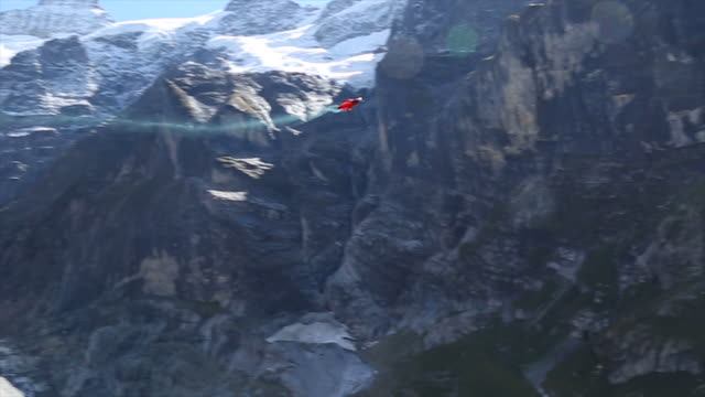 Wingsuit flier soars between valley and snow capped mountains