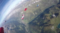 Wingsuit fliers soar through tranquil skies above mountain landscape