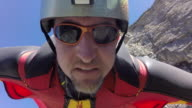 POV of wingsuit flyer jumping off cliff