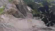 Wingsuit flyer jumps from cliff edge, flying over mountains