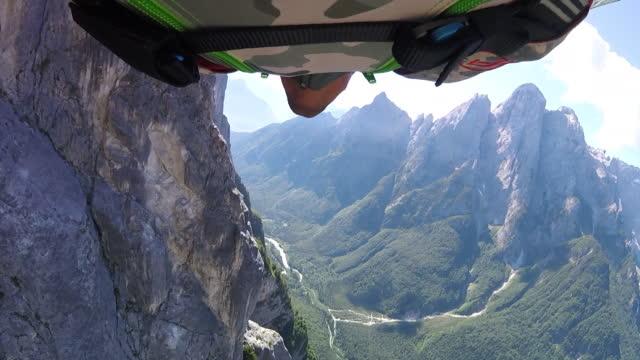 POV of wingsuit pilot flying along mountain cliffs