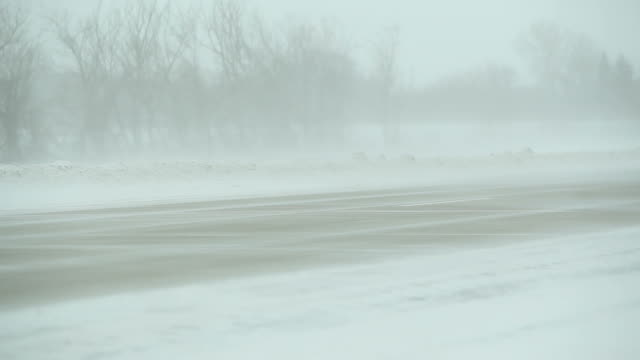 Winter Blizzard with Blowing Snow Across Highway and Vehicles