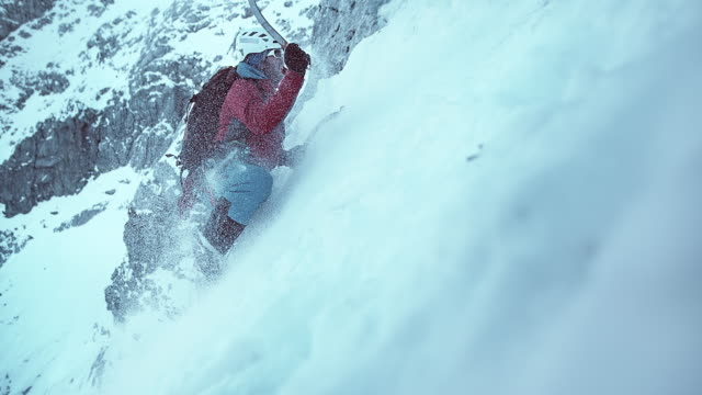 SLO MO vintern klättraren svängande hans yxa att klättra snöiga backen