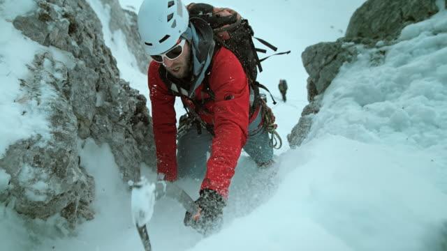 LD Winter klimmer met bijl opstijgen sneeuw bedekt helling