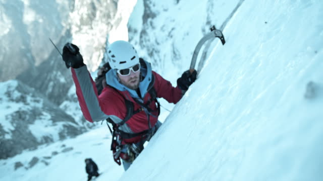 SLO MO winter klimmer met behulp van zijn ijsbijl