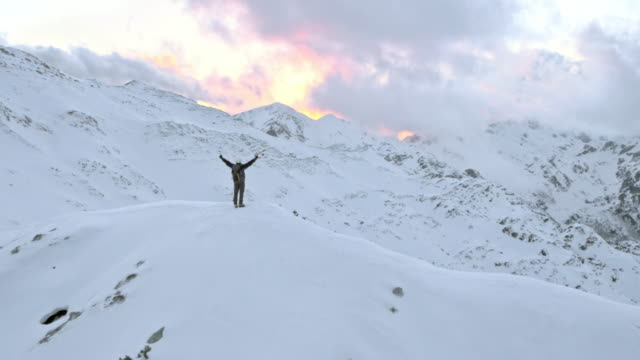 AERIAL Winter mountaineer victoriously raising his hands on mountain top