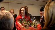 Amy Williams returns to the UK ***FLASH ENGLAND London Heathrow Airport INT Amy Williams walking through Heathrow Airport carrying bouquet of flowers...