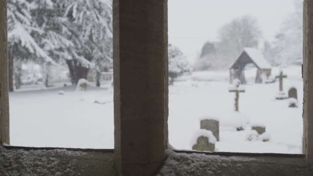 Winter snow falls onto village church and graveyard, Oxfordshire, England