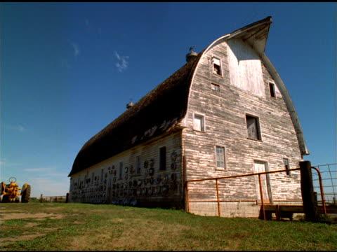 Wispy clouds pass over barn, Wyoming