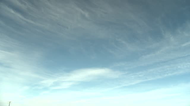 Wispy white clouds drift through the blue sky. Available in HD.