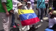 With one hand for their rosaries and the other holding up a Venezuelan flag nuns Esperanza Cadavid and Leonor Perez joined the opposition...