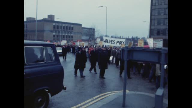 Wolverhampton GV Marchers and banners towards with police Zoom In MS Marchers LR MS Small group proNat Front on pavement pan motorcycle and foot...