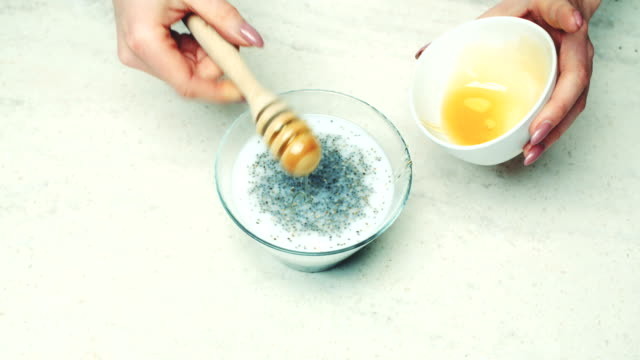 Woman Adding Honey And Mixing Ingredients In Bowl