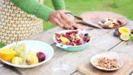 Woman adding seasonings to cut-up fruits