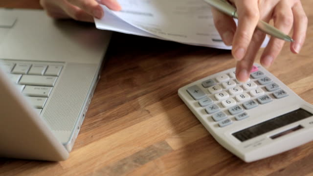 Woman Adding Up Domestic Bills With Calculator