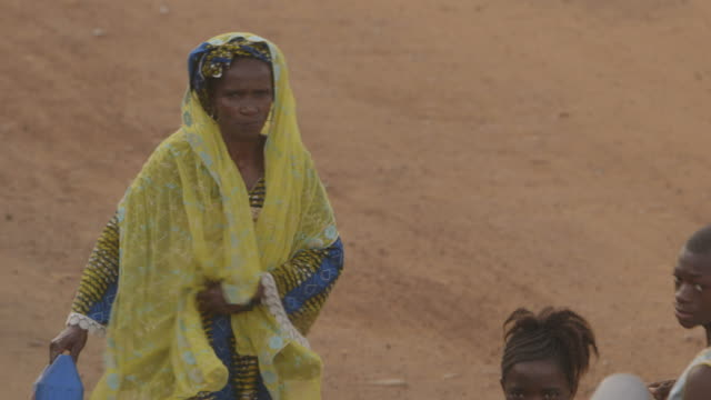 A woman adjusts her yellow headscarf whilst walking along a Sierra Leonean street.