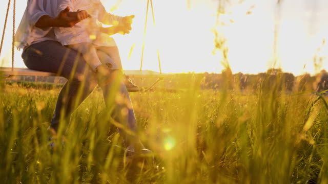 SLO MO Woman and baby girl swinging at sunset