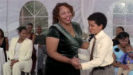 Woman and boy dancing at wedding reception inside tent / Arizona
