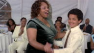 Woman and boy dancing at wedding reception inside tent / guests sitting at tables clapping / Arizona