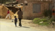 WS PAN Woman and boy walking down street past construction site / Bogota, Colombia