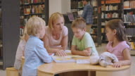 DS Woman and children reading a book in a public library