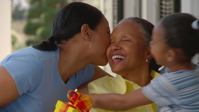 CU PAN Woman and girl hugging and kissing her grandmother while holding gift and bouquet / Richmond, Virginia, USA