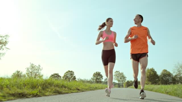 SLO MO TS di donna e uomo che corre in verde circostante