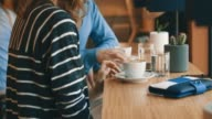 Woman and man using digital tablet in cafe