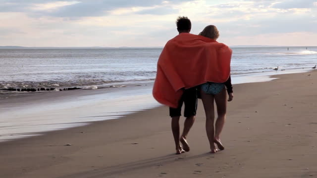 MS PAN TS Woman and man walking on beach and towel wrapping around their shoulders / Rockaway, New Jersey,United States