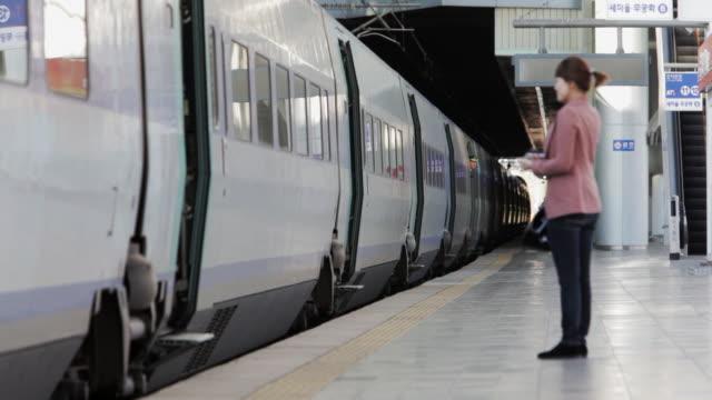 LS Woman and man waving goodbye to passengers on KTX high-speed train leaving Seoul Station / Seoul, South Korea
