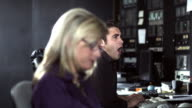 R/F CU Woman and man working in television broadcasting control room, Dallas, Texas, USA