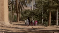 A woman and several children walk along a dirt path under a grove of palm trees.
