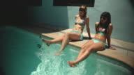 WS Woman and teenage girl (14-15) sitting on edge of pool / Los Angeles, California, USA