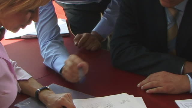 CU, Woman and two men doing paperwork at desk in office, close-up of hands