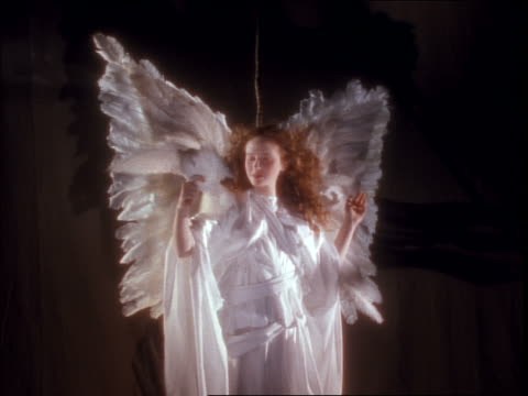 Woman angel in white holding white dove / wind blowing