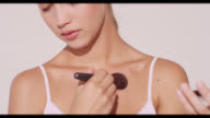 A woman applies bronzer to collarbone area
