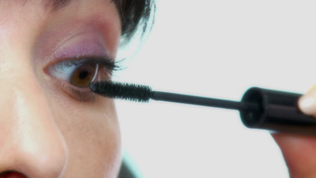 ECU, Woman applying mascara