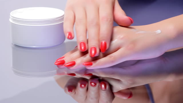 Woman Applying Skin Moisturizer on Hands.