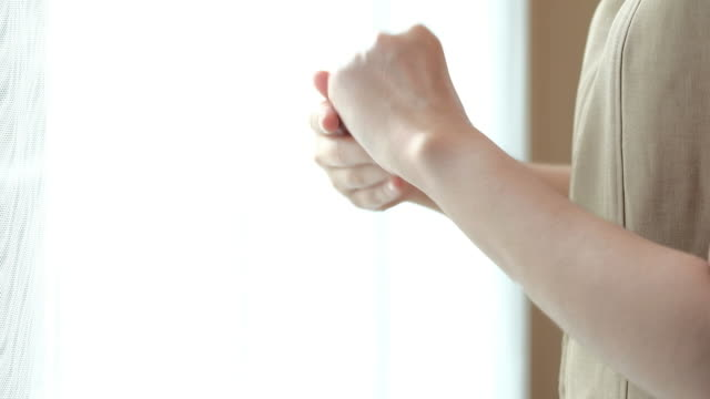 4K : woman applying skin moisturizing cream with hands.