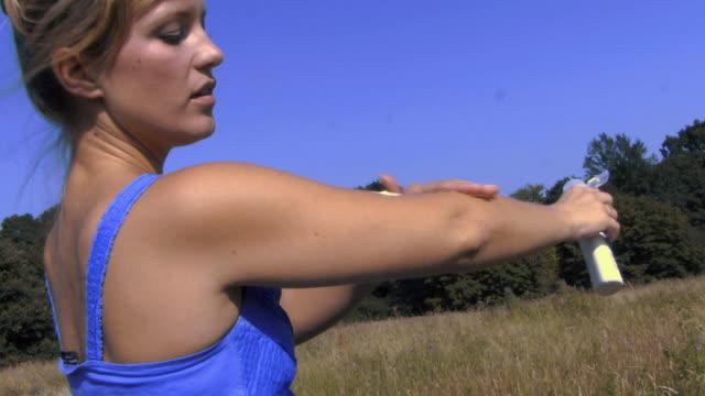 MS Woman applying sun cream in field / Hampstead, United Kingdom