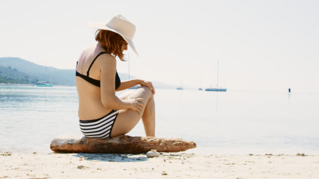WS-Frau Sonnencreme Eincremen am Strand