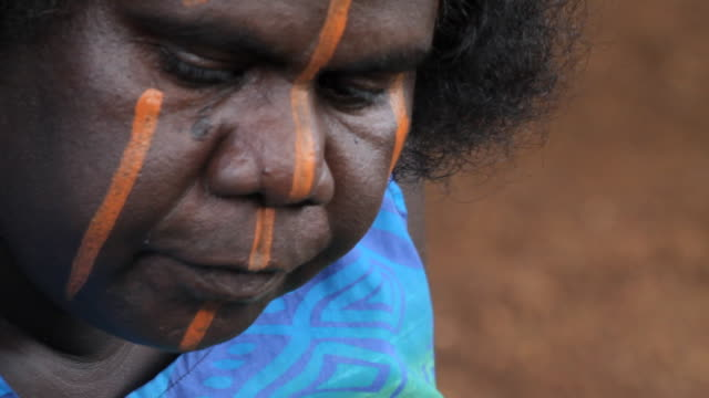 CU ZO TU TD Woman applying traditional paint to her face on tiwi islands / Northern Territory, Australia