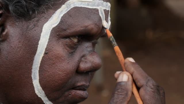 CU Woman applying traditional paint to her face on tiwi islands / Northern Territory, Australia