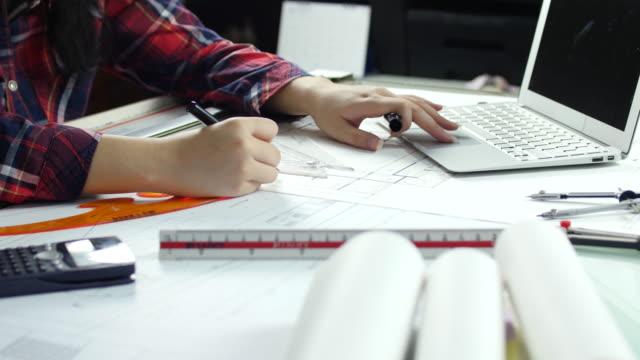 Kvinna arkitekt arbetar och ritning med blueprint lakan, kvinna i arbete