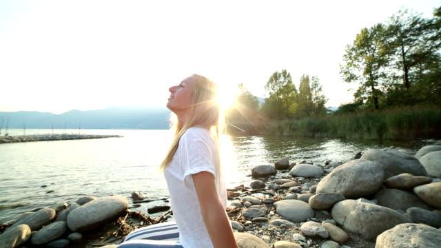 Kvinna armarna utsträckta i solnedgången